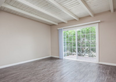 Living room with french door opening to the balcony and exposed beams
