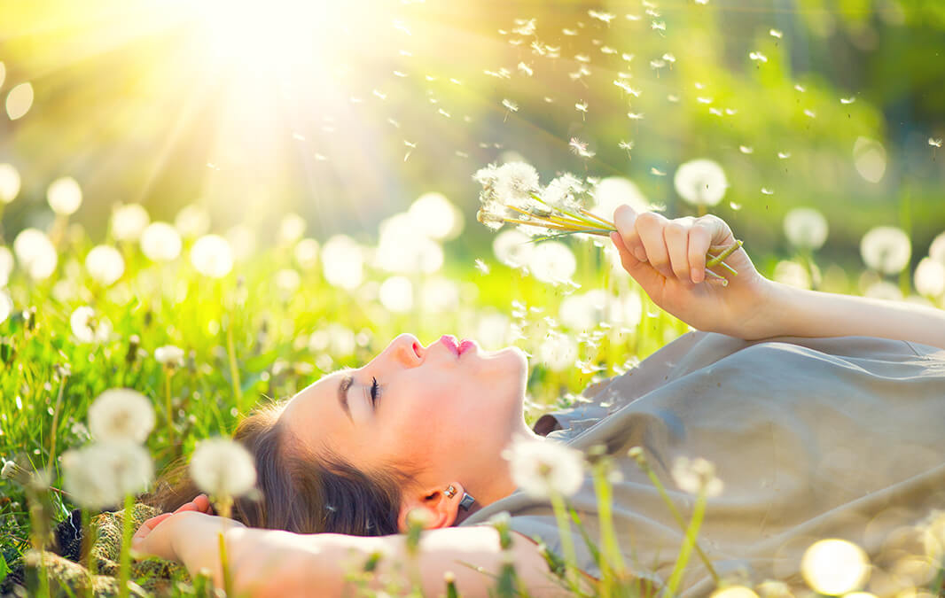 A woman blowing dandelions lying down