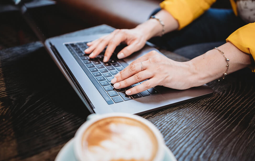 Hands typing on keyboard with mug of coffee